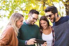 Groupe d'amis de sourire avec le comprimé numérique Photo stock