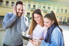 Groupe d'amis de sourire avec le comprimé numérique Photos libres de droits