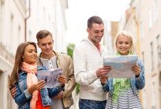 Groupe d'amis de sourire avec le guide et la carte de ville Photo libre de droits