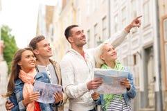 Groupe d'amis de sourire avec le guide et la carte de ville Photographie stock