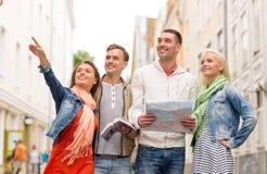 Groupe d'amis de sourire avec le guide et la carte de ville Images stock