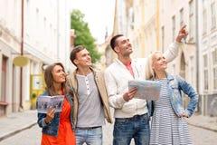 Groupe d'amis de sourire avec le guide et la carte de ville Image libre de droits