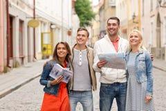 Groupe d'amis de sourire avec le guide et la carte de ville Photographie stock libre de droits