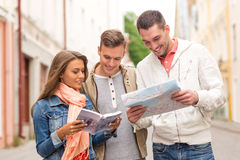 Groupe d'amis de sourire avec le guide et la carte de ville Photos libres de droits
