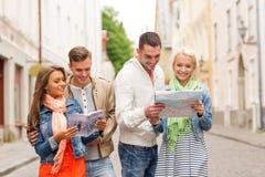Groupe d'amis de sourire avec le guide et la carte de ville Photos stock