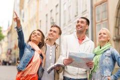 Groupe d'amis de sourire avec le guide et la carte de ville Image stock