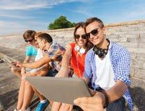 Groupe d'amis de sourire avec le PC de comprimé dehors Images stock