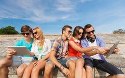 Groupe d'amis de sourire avec le PC de comprimé dehors Photographie stock libre de droits