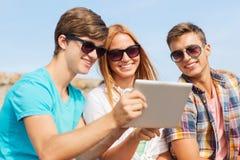 Groupe d'amis de sourire avec le PC de comprimé dehors Image stock