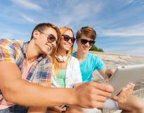 Groupe d'amis de sourire avec le PC de comprimé dehors Photographie stock