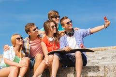 Groupe d'amis de sourire avec le smartphone dehors Photos stock