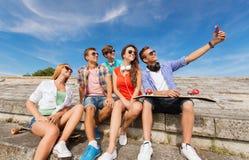 Groupe d'amis de sourire avec le smartphone dehors Photo stock