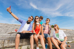 Groupe d'amis de sourire avec le smartphone dehors Photographie stock libre de droits