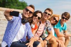 Groupe d'amis de sourire avec le smartphone dehors Images stock