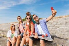 Groupe d'amis de sourire avec le smartphone dehors Image libre de droits