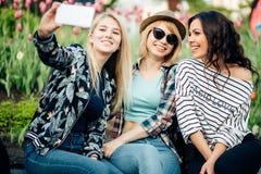 Groupe d'amis de sourire avec le smartphone photographiant et prenant le selfie Photographie stock