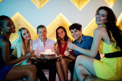 Groupe d'amis de sourire ayant un verre de champagne tout en célébrant l'anniversaire Photographie stock libre de droits