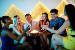 Groupe d'amis de sourire ayant un verre de champagne tout en célébrant l'anniversaire Photo stock