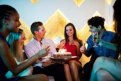 Groupe d'amis de sourire ayant un verre de champagne tout en célébrant l'anniversaire Image stock