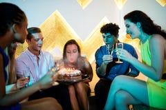 Groupe d'amis de sourire ayant un verre de champagne tout en célébrant l'anniversaire photos stock