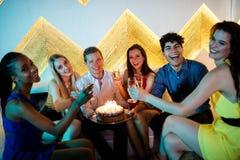 Groupe d'amis de sourire ayant un verre de champagne tout en célébrant l'anniversaire Images stock