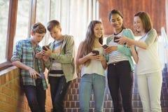 Groupe d'amis de sourire d'école à l'aide du téléphone portable dans le couloir Photographie stock libre de droits