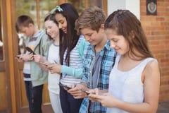 Groupe d'amis de sourire d'école à l'aide du téléphone portable dans le couloir Image stock