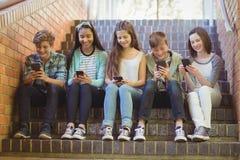 Groupe d'amis de sourire d'école s'asseyant sur l'escalier utilisant le téléphone portable Image libre de droits
