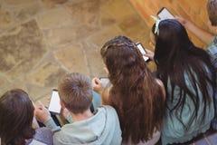 Groupe d'amis de sourire d'école s'asseyant sur l'escalier utilisant le téléphone portable Image stock