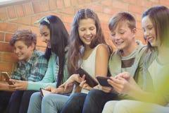 Groupe d'amis de sourire d'école s'asseyant sur l'escalier utilisant le téléphone portable Photo stock