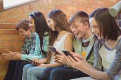 Groupe d'amis de sourire d'école s'asseyant sur l'escalier utilisant le téléphone portable Photo libre de droits