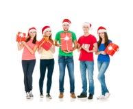 Groupe d'amis de sourire dans des chapeaux de Noël Photographie stock libre de droits