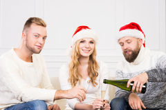 Groupe d'amis de sourire dans la célébration de chapeaux de Noël Photographie stock