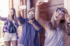 Groupe d'amis de sourire dans le fichier unique prenant le selfie drôle Images stock