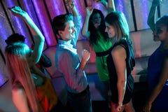 Groupe d'amis de sourire dansant sur la piste de danse Images stock