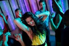 Groupe d'amis de sourire dansant sur la piste de danse Photos stock