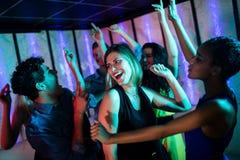 Groupe d'amis de sourire dansant sur la piste de danse Photos libres de droits