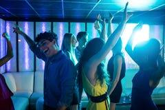 Groupe d'amis de sourire dansant sur la piste de danse Images libres de droits