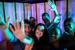 Groupe d'amis de sourire dansant sur la piste de danse Image libre de droits
