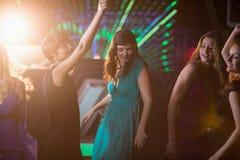 Groupe d'amis de sourire dansant sur la piste de danse Photographie stock