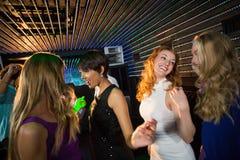 Groupe d'amis de sourire dansant sur la piste de danse Image stock