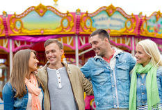 Groupe d'amis de sourire en parc d'attractions Image libre de droits
