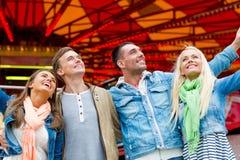 Groupe d'amis de sourire en parc d'attractions Image stock
