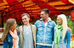 Groupe d'amis de sourire en parc d'attractions Images stock