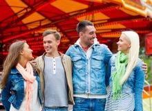 Groupe d'amis de sourire en parc d'attractions Photos stock