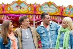 Groupe d'amis de sourire en parc d'attractions Photographie stock libre de droits