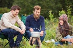 Groupe d'amis de sourire faisant cuire la nourriture dehors Photographie stock libre de droits