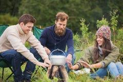 Groupe d'amis de sourire faisant cuire la nourriture dehors Images libres de droits