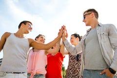 Groupe d'amis de sourire faisant la haute cinq dehors Images stock
