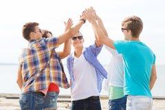 Groupe d'amis de sourire faisant la haute cinq dehors Photo libre de droits